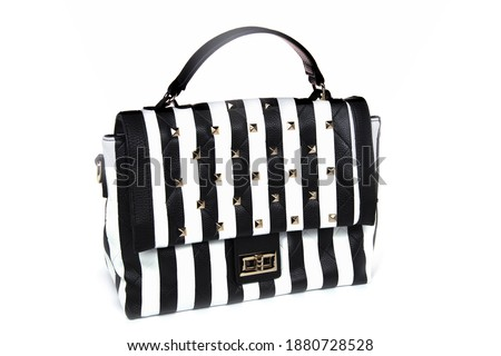 Photo of  Striped women's bag isolated on white background. Female's black and white elegant purse with stripes.