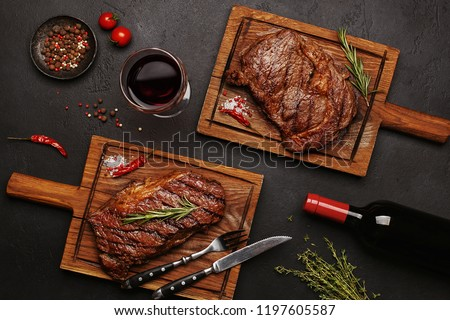 Striploin and Ribeye grilled beef steaks served on wooden boards with glass of wine, bottle of wine, herbs and spices. Top view
