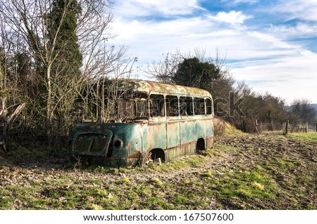 stripped rusty, old abandoned red bus wreck in the north of France