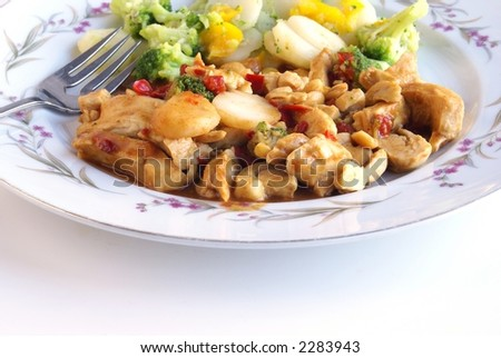 Strips of chicken meat with red peppers an peanuts in kung pao sauce. Broccoli, water chestnuts and yellow peppers compliment this nice asian inspired healthy meal. White background with copy space.