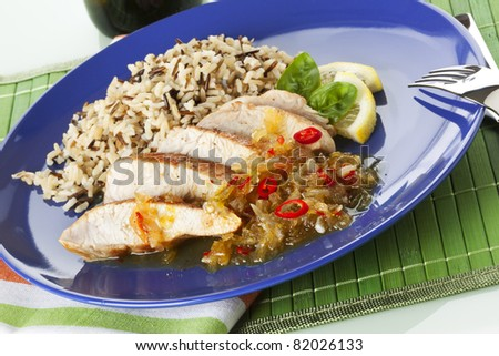 strips of fried turkey breast with a sauce of lemon, chili pepper, onions and garlic, arranged with wild rice on blue plate