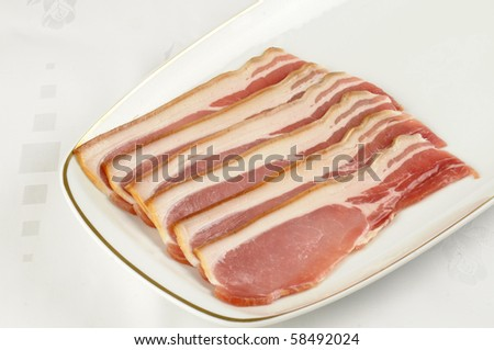 strips of uncooked smoked back bacon on a white serving plate