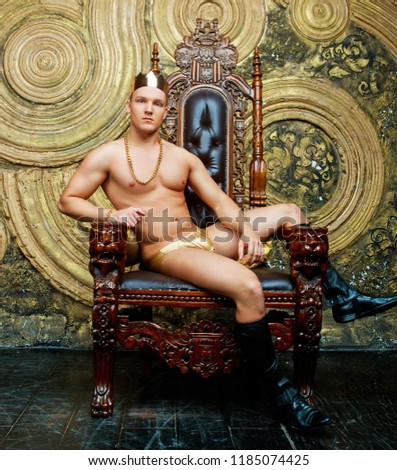 striptease dancer wearing costume with a golden crown in the studio against golden studio background