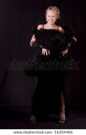 Striptease Series #1: Beautiful Blonde in Black Velvet Evening Gown. - stock photo