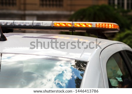 Strobe light flashes orange, mounted on a police car #1446413786