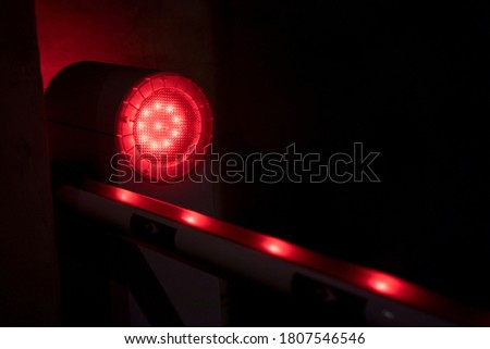 Photo of  Strobe light with red pulsating neon dots traveling along a line