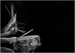 Stroboscopic B&W action photo of a drummer's drumsticks hitting and rebounding on a snare drum.