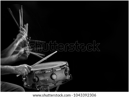 Stroboscopic B&W action photo of a drummer's drumsticks hitting and rebounding on a snare drum. #1043392306