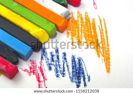 strokes of pastel crayons and crayons in different colors on a white paper sheet #1558212038