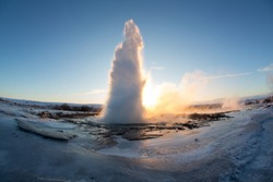 Strokkur Geysir geyser on the south west Iceland. Famous tourist attraction Geysir on route 35 in sunrise. High eruption of boiling water at geothermal area Haukadalur. Water fountain in winter.