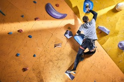 Strong active man with physical disability enjoys bouldering hobby, bought membership to the new modern climbing sport center, trains every weekend. Extreme hobby concept.