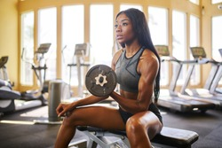 strong african american woman lifting weights in gym