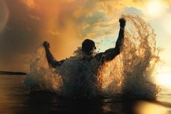 Strong and athletic man jumps out of the water at sunset, flying a lot of splashing