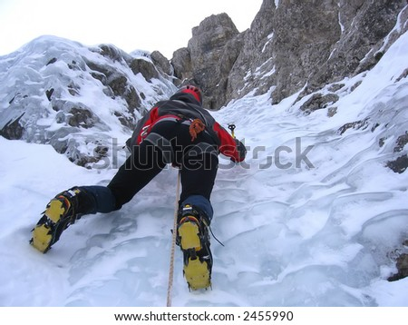 Strong and brave young girl, during ascent in a frozen waterfall.