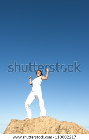 Strong and confident attractive mature woman on top of a mountain, isolated with blue sky as background and copy space.