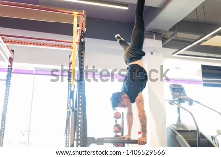 Strong and determined man doing handstand on bars at health club