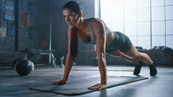 Strong and Fit Athletic Woman in Sport Top and Shorts is Doing Push Up Exercises in a Loft Style Industrial Gym with Motivational Posters. It's Part of Her  Fitness Training Workout.