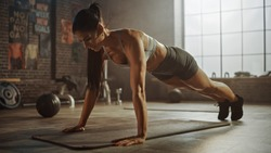 Strong and Fit Athletic Woman in Sport Top and Shorts is Doing Push Up Exercises in a Loft Style Industrial Gym with Motivational Posters. It's Part of Her  Fitness Training Workout. Warm Light.