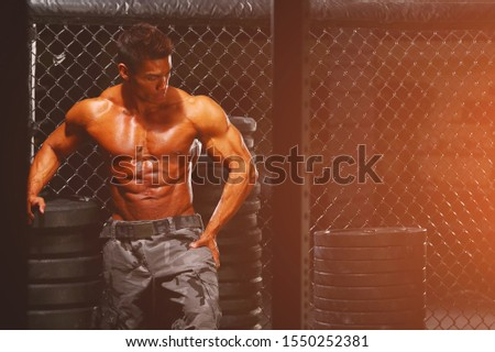 Strong and handsome athletic young man with muscles abs and biceps. Close-up of a power fitness man.