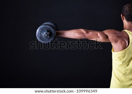 Strong and muscular guy with dumbbell over black background