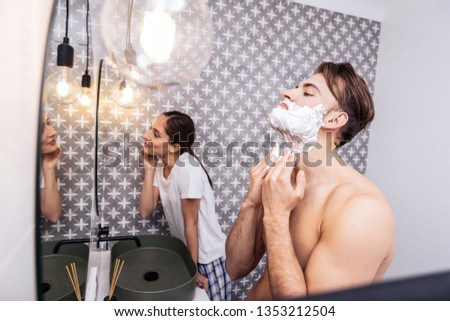 Strong and sexy. Strong sexy dark-haired husband shaving his face standing near his lovely woman