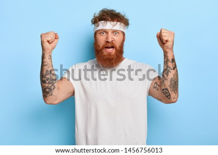 Strong angry sportsman with red hair, raises tattooed arms, shows his power, exclaims with dissatisfaction, wears white headband and t shirt, isolated on blue background. Sport and strength.