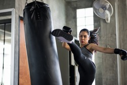 Strong Asian boxing woman jump kick to huge punching bag at fitness gym. Athletic girl training Muay Thai boxing for bodybuilding and healthy lifestyle concept. workout in sport club.