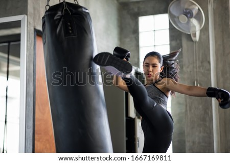 Strong Asian boxing woman jump kick to huge punching bag at fitness gym. Athletic girl training Muay Thai boxing for bodybuilding and healthy lifestyle concept. workout in sport club. Stock photo ©