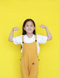 Strong asian little kid girl raising hands up and smiling. Portrait of happy child in dungarees isolated on yellow background.