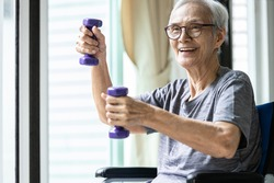 Strong asian senior woman working out with heavy dumbbells,lifting dumbbell weights for strength training,fitness elderly people doing exercise while sit in wheelchair,health care,healthy lifestyle