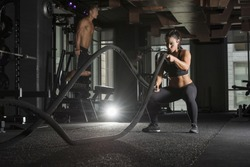 Strong athlete woman wearing a black sports bra and long tights in a dark gym with a muscular male in the background  using  battle ropes for exercise