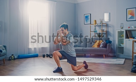 Strong Athletic Fit Man in T-shirt and Shorts is Doing Forward Lunge Exercises at Home in His Spacious and Bright Apartment with Minimalistic Interior.