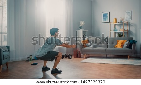 Strong Athletic Fit Man in T-shirt and Shorts is Doing Squat Exercises at Home in His Spacious and Bright Apartment with Minimalistic Interior.