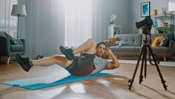 Strong Athletic Fit Man in T-shirt and Shorts is Recording his Crisscross Crunch Workout on Camera for His Blog. Scene takes place in His Spacious and Bright Living Room with Minimalistic Interior.