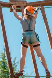 Strong athletic girl in orange helmet with rope belay and harness overcomes obstacle course for climbing, view rear. Overcoming difficulties and fear, sport challenge. Summer extreme sports