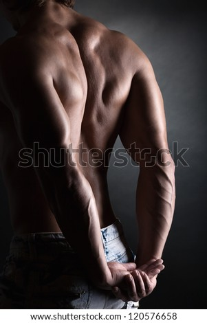 Strong athletic man back on dark background