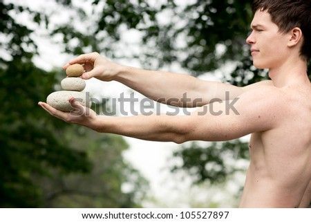Strong athletic man holding a pile of stones in balance. Get the balance concept.