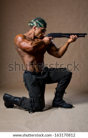 Strong athletic man with a gun. Special Forces soldier takes aim