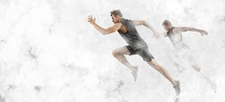 Strong athletic men sprinter running on white smoke background wearing in sportswear. Sport and fitness motivation