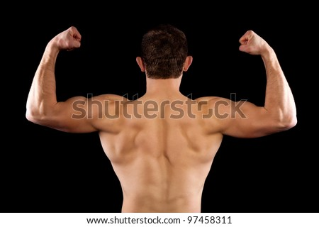 strong athletic muscle man, sports guy showing his male muscles, standing back isolated on black background