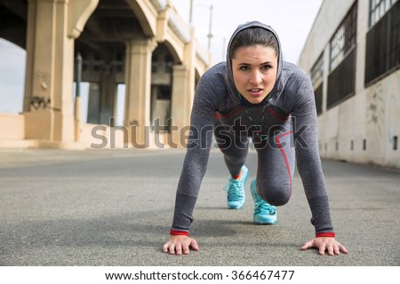 Strong athletic toned female athlete in sportswear with hoody training with push ups outdoors