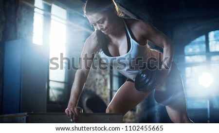 Strong Athletic Woman Does Dumbbell Bench Press Exercise as Part of Her Cross Fitness Bodybuilding Gym Exercise.