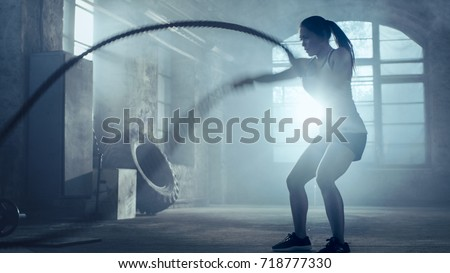 Stock Photo Strong Athletic Woman Exercises with Battle Ropes as Part of Her Fitness Gym Workout Routine. She's Covered in Sweat and Training Takes Place in a Abandoned Factory Remodeled into Gym.