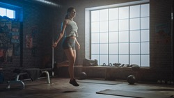 Strong Athletic Woman Exercises with Jumping Rope in a Loft Style Industrial Gym. She's Concentrated on Her Intense  Fitness Training Program. Facility has Motivational Posters on the Wall.