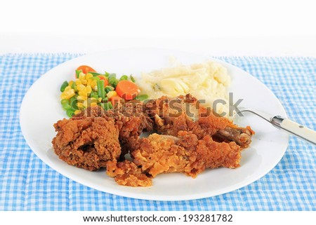 Strong back lighting on Three pieces of chicken with crunchy breading and deep-fried and served with mashed potatoes and mixed vegetable medley.