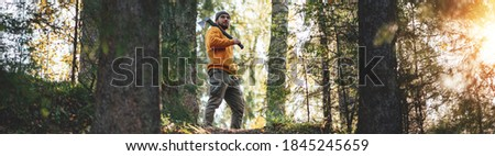 Strong bearded lumberman wearing work clothes holds axe on his shoulder. Wide image Stock photo ©