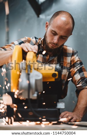 Strong bearded man working on electrical angular grinding machine in metalworking. Work in action. Sparks fly apart. Vertical