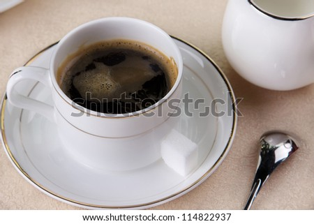 Strong black freshly brewed coffee in a cup and saucer with spoon and a small milk jug to the side
