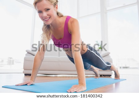 Strong blonde in plank position on exercise mat smiling at camera at home in the living room