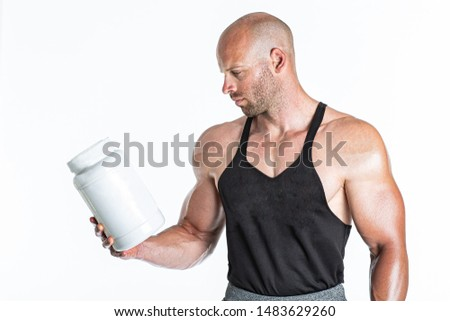Strong bodybuilder holding a plastic jar with a dry whey protein. Isolated on white background in studio. Concept sports nutrition
